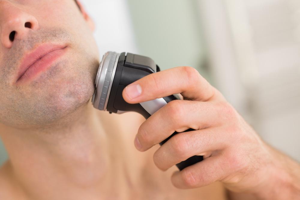 mężczyzna golący zarost elektryczną golarką