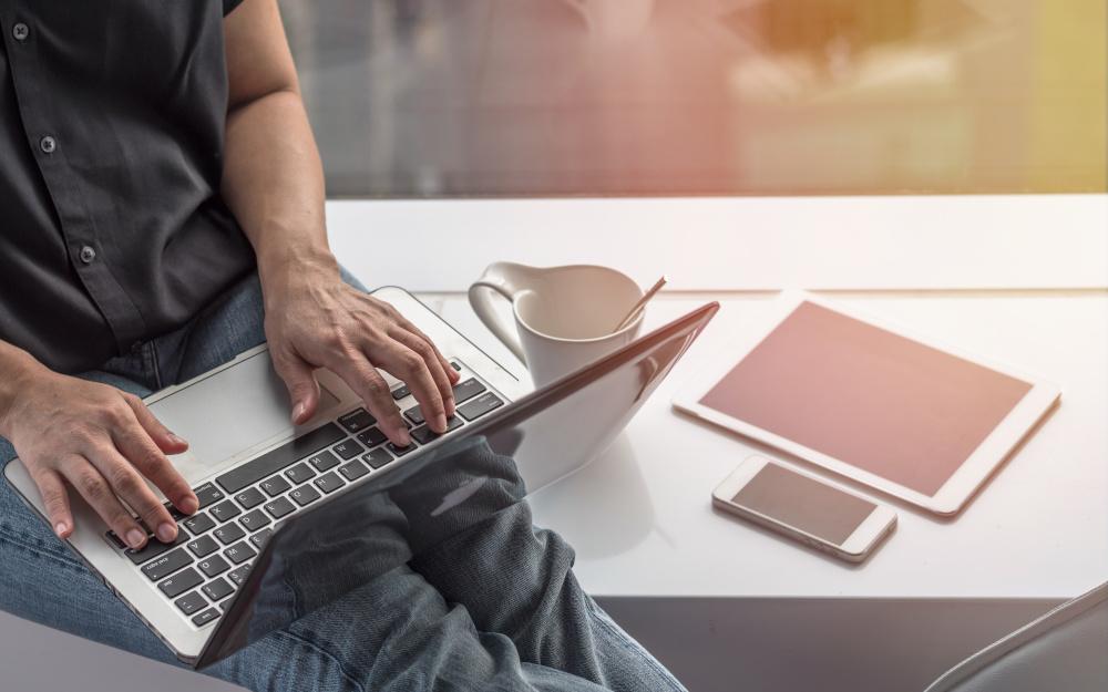 mężczyzna wykonujący pracę przed laptopem