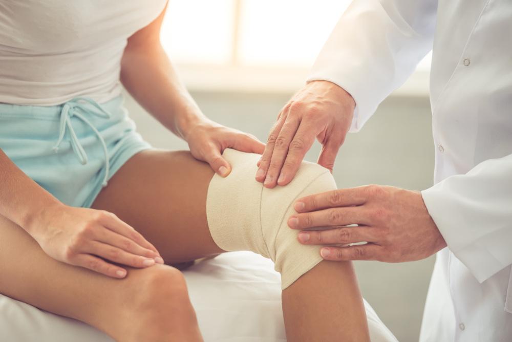 doktor sprawdzający kolano pacjentki