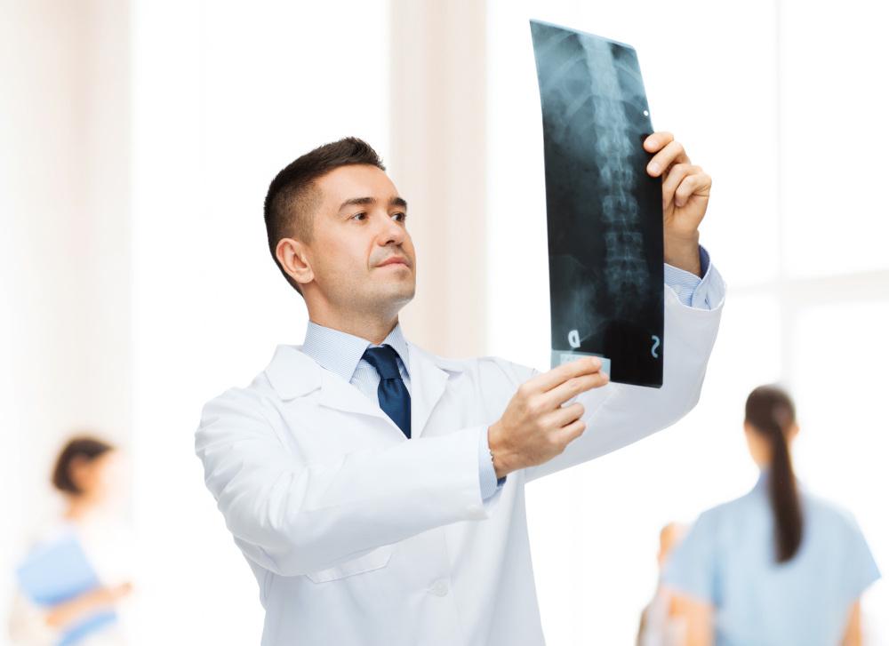 lekarz analizującyc zdjęcia rentgenowskie kręgosłupa