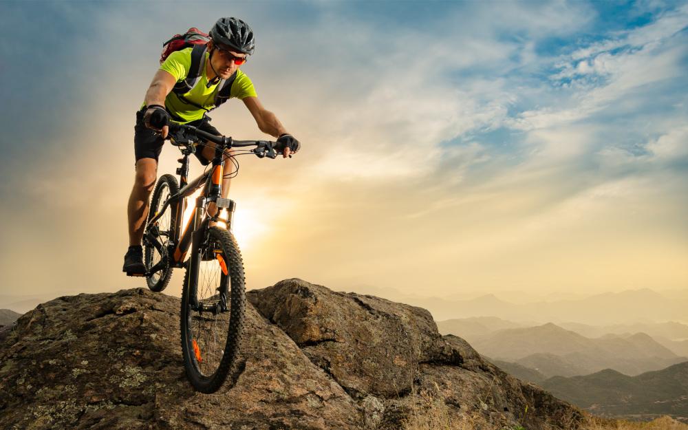 mężczyzna jeżdżący na rowerze po wzgórzach