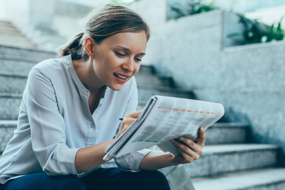 kobieta szukająca ogłoszeń w prasie