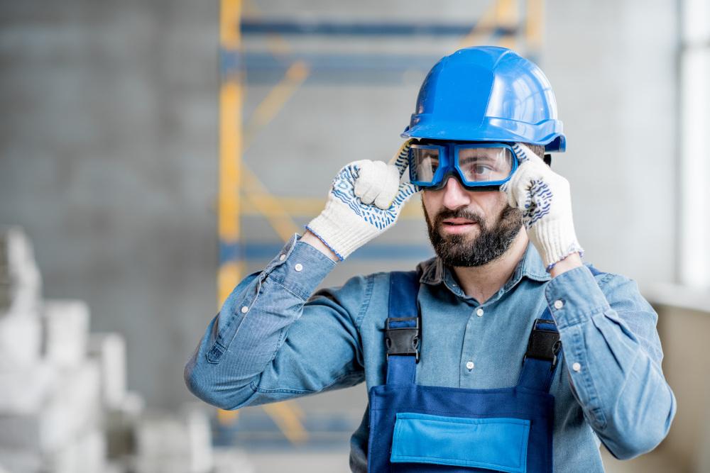 mężczyzna wkładający okulary ochraniające oczy na terenie budowy