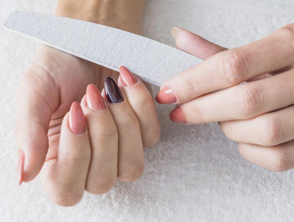 kobieta piłująca paznokcie
