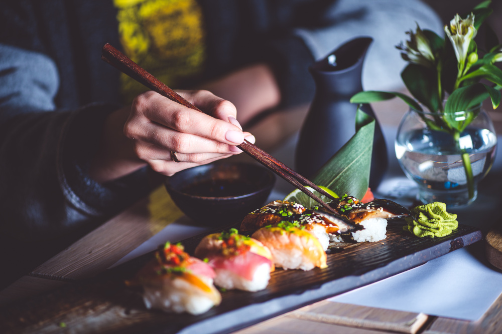 mężczyzna jedzący sushi pałeczkami