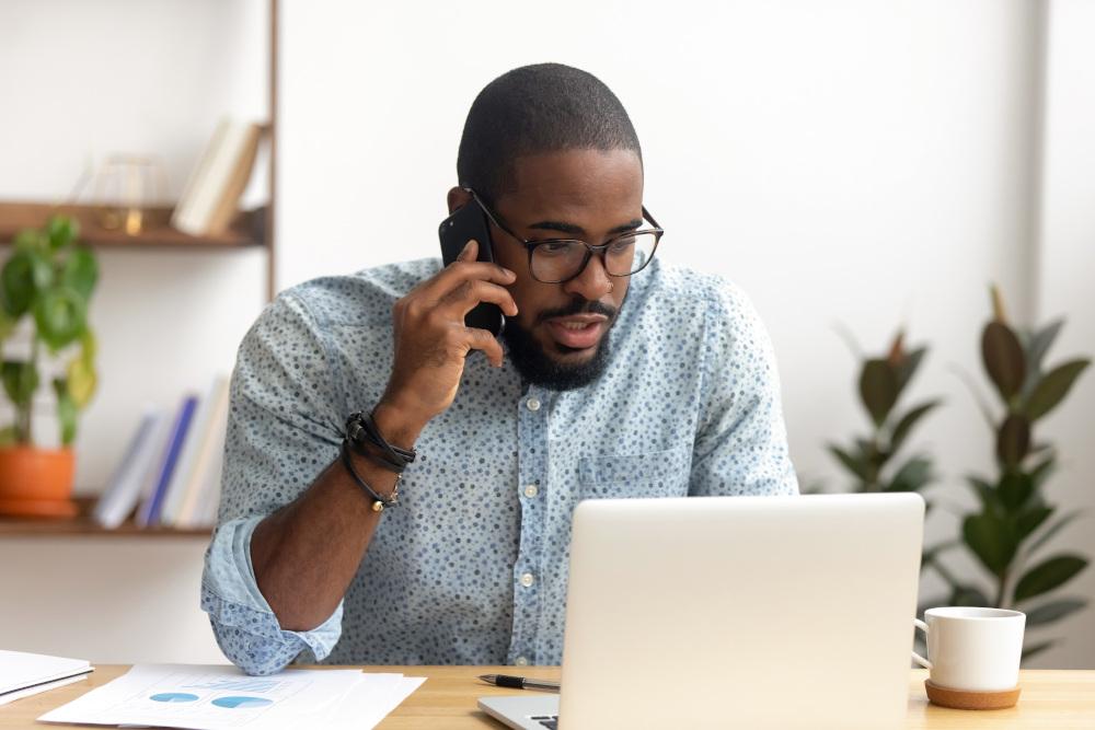 mężczyzna dzwoniący przez telefon i siedzący przed laptopem