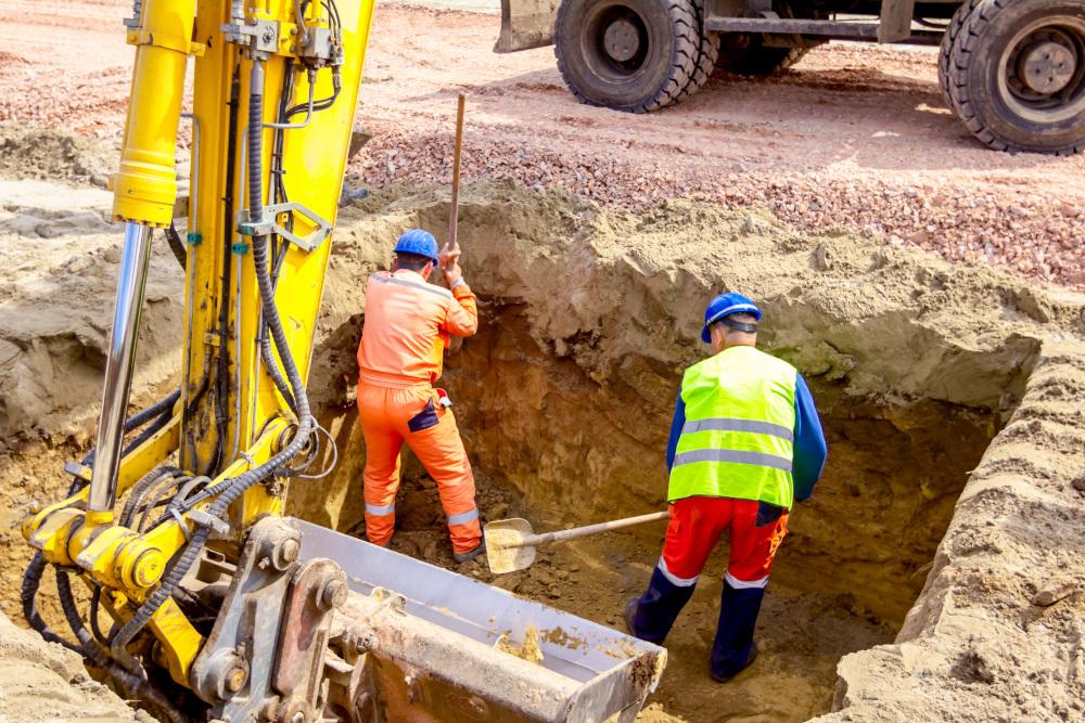 kopanie fundamentów przez pracowników z zastosowaniem koparki