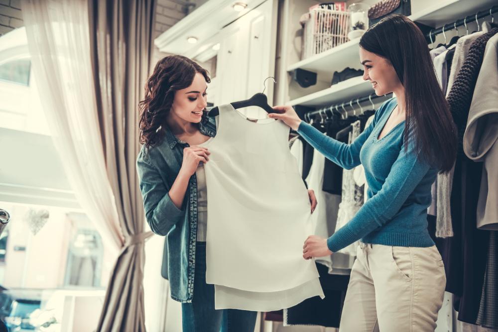 kobieta wybierająca ubrania w butiku rozmawiająca z inna kobietą